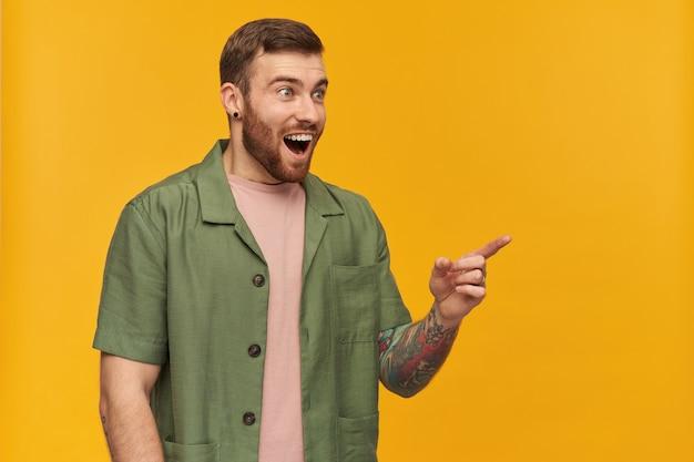 Retrato de homem espantado com cabelo castanho e cerdas. jaqueta verde de mangas curtas. tem tatuagem. observando e apontando o dedo para a direita no espaço da cópia, isolado sobre a parede amarela
