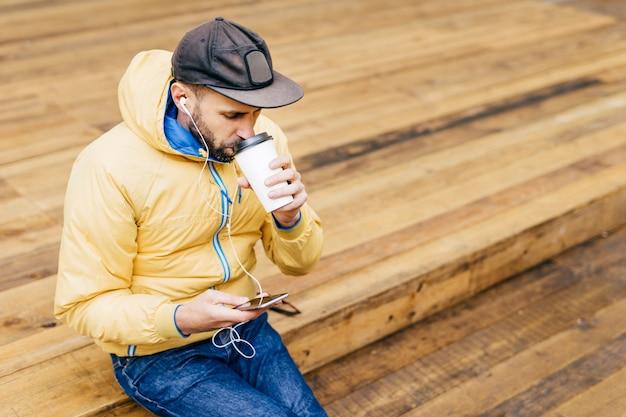 Retrato de homem estiloso com barba, boné, jaqueta amarela e calça jeans, bebendo café delicioso