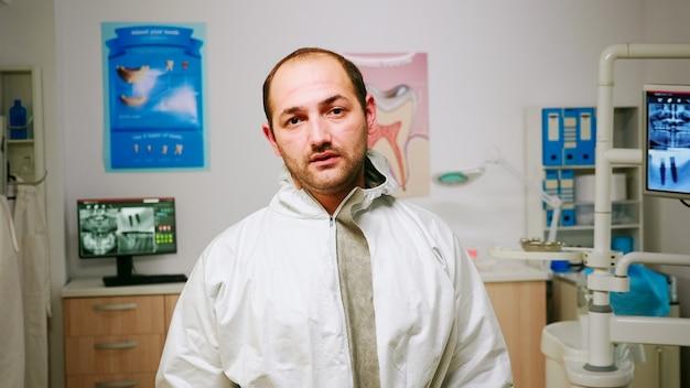 Retrato de homem estomatologista exausto tirando a proteção facial, olhando para a câmera, sentado no novo consultório odontológico normal. enfermeira pediátrica falando com o paciente criança em segundo plano.