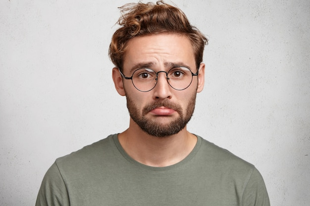 Retrato de homem estressado e frustrado curva o lábio inferior sendo abusado por alguém, tem acesso de raiva