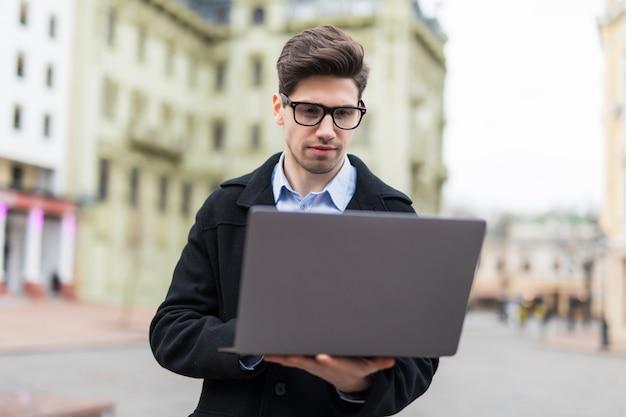 Retrato de homem estudante universitário usar laptop no campus