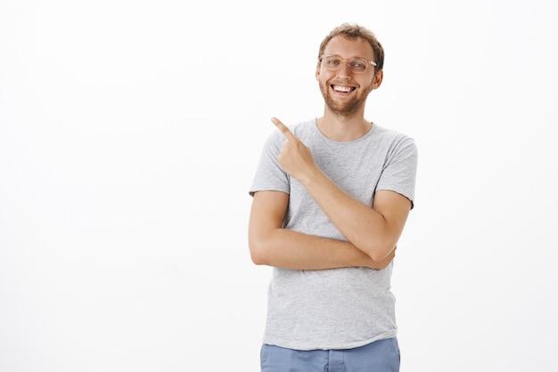 Retrato de homem europeu bonito, alegre e despreocupado com cerdas nos óculos, sorrindo e rindo casualmente, tendo um ótimo dia apontando para o canto superior esquerdo com olhar satisfeito e encantado sobre a parede branca