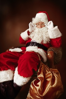 Retrato de homem fantasiado de papai noel com uma luxuosa barba branca, chapéu de papai noel e uma fantasia vermelha em vermelho