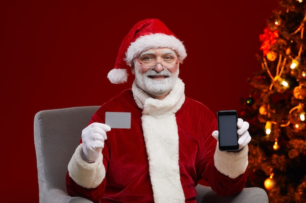 Retrato de homem fantasiado de papai noel segurando um cartão de visita e um celular nas mãos