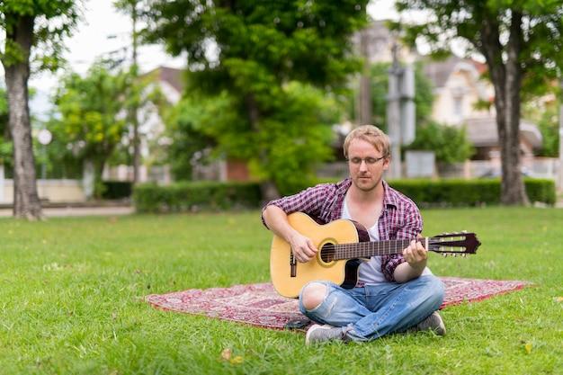 Retrato de homem fazendo piquenique enquanto toca violão ao ar livre