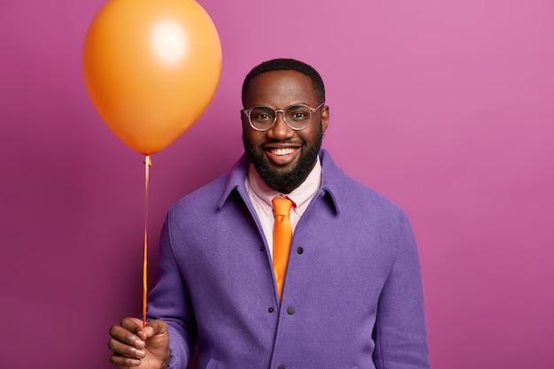 Retrato de homem feliz chega na despedida de solteiro, fica com um balão laranja, sorri amplamente, estando em clima de festa, parabeniza amigo