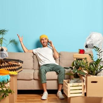Retrato de homem feliz conversa ao telefone, gesticula com uma das mãos, tenta explicar o caminho para seu novo apartamento e usa chapéu amarelo