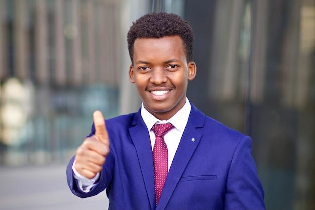 Retrato de homem feliz e positivo, negro africano afro-americano jovem empresário em terno formal com gravata sorrindo largamente aparecendo o polegar para cima, como gesto. conceito de negócios.