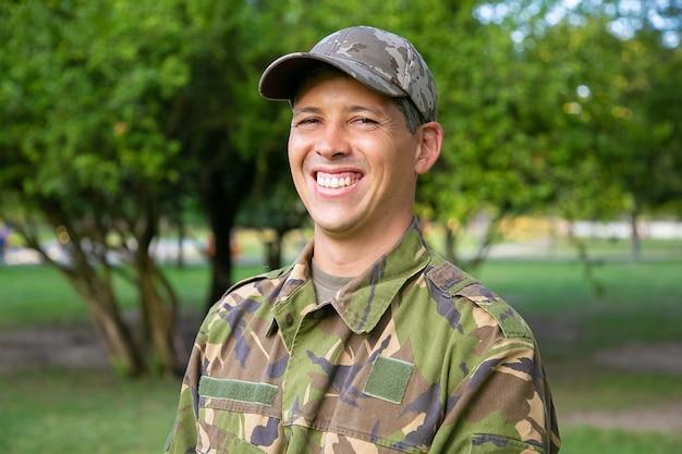Retrato de homem feliz em uniforme de camuflagem militar em pé no parque.