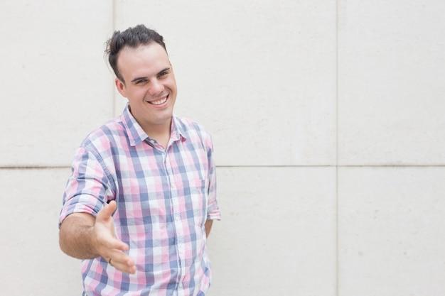 Retrato de homem feliz esticando mão para saudação