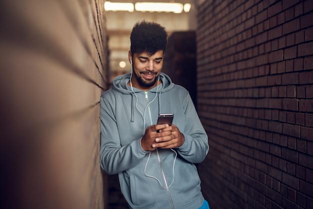 Retrato de homem feliz jovem bonito afro-americano motivado hipster com fones de ouvido em pé no meio de duas paredes de tijolo, enquanto inclinando-se contra um e segurando móvel.