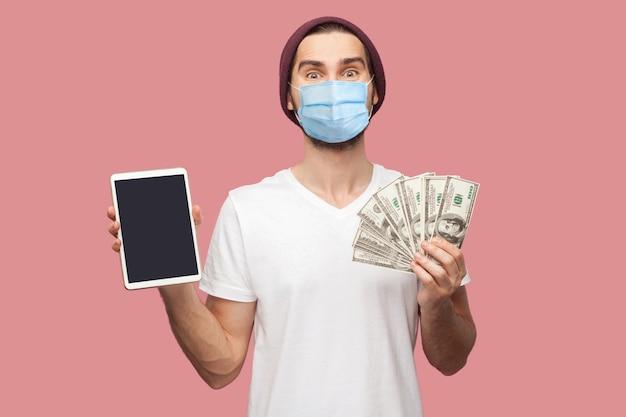 Retrato de homem feliz jovem hippie com máscara médica cirúrgica na camisa branca e chapéu casual em pé, segurando o ipad de tela vazia e a caixa de presente verde. interior, isolado, foto de estúdio, fundo rosa