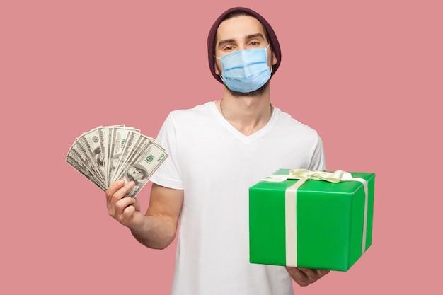 Retrato de homem feliz jovem hippie com máscara médica cirúrgica na camisa branca e chapéu casual em pé, segurando um leque de dólares em dinheiro e caixa de presente verde. interior, isolado, foto de estúdio, fundo rosa