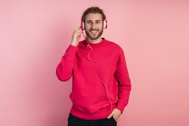 Retrato de homem feliz, ouvindo música com fones de ouvido.