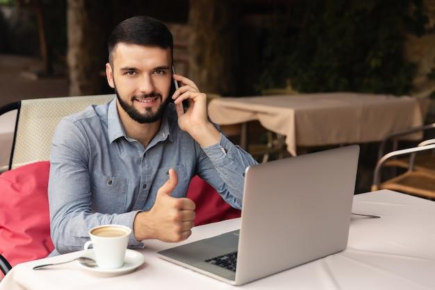 Retrato de homem feliz que trabalha em casa, ele se senta com uma xícara de café na mesa, falando em um telefone inteligente