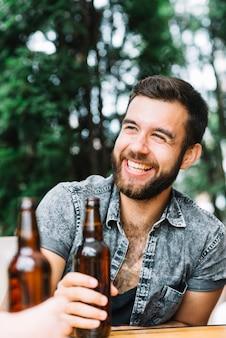 Retrato, de, homem feliz, segurando, garrafa cerveja marrom, em, mão