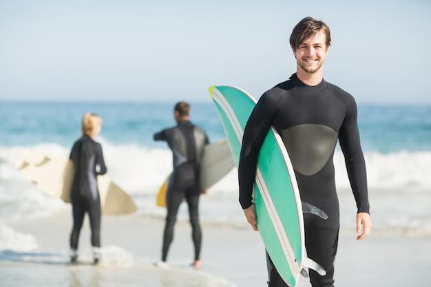 Retrato de homem feliz, segurando uma prancha de surf na praia