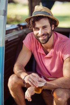 Retrato de homem feliz sentado na caravana com copo de cerveja