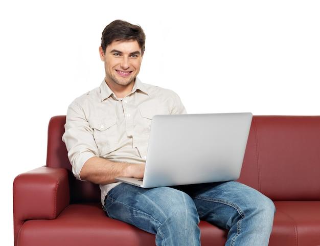 Retrato de homem feliz sorridente com laptop senta-se no divã, isolado no branco.