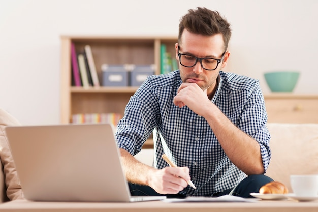 Retrato de homem focado trabalhando em casa