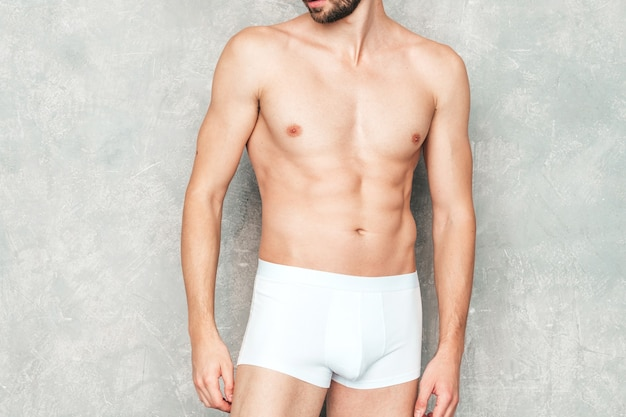 Retrato de homem forte bonito desportivo. modelo de aptidão atlética saudável posando perto de uma parede cinza na cueca branca.