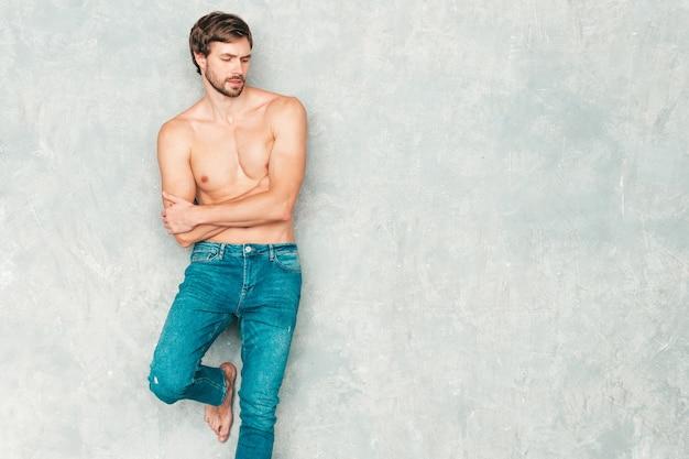Retrato de homem forte bonito desportivo. modelo de aptidão atlética sorridente saudável posando perto de uma parede cinza em jeans.