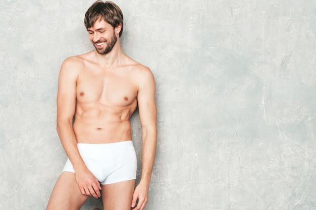Retrato de homem forte bonito desportivo. modelo de aptidão atlética sorridente saudável posando perto de uma parede cinza na cueca branca.