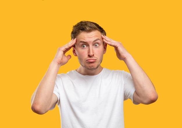 Retrato de homem frustrado. ataque de pânico. estressado cara tocando a cabeça isolada em fundo laranja.