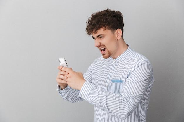 Retrato de homem furioso e irritado, vestido com uma camisa, expressando raiva enquanto segura e usa o smartphone isolado sobre a parede cinza