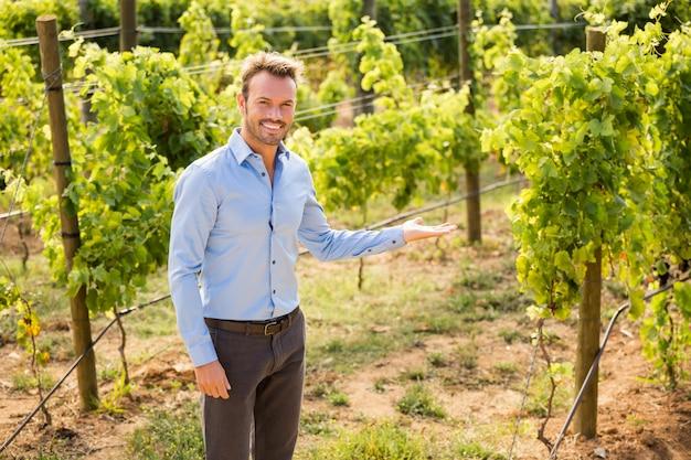 Retrato de homem gesticulando em vinhedo
