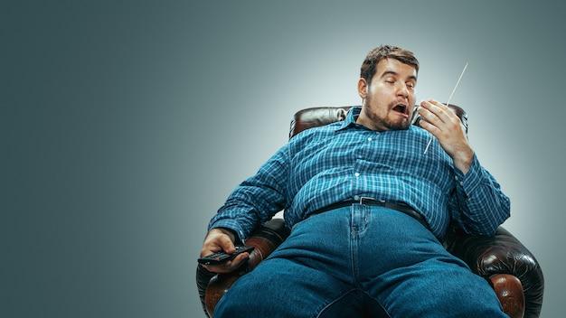 Retrato de homem gordo caucasiano vestindo jeans e whirt sentado em uma poltrona marrom isolada em um fundo cinza gradiente. emocional assistindo tv e mudando de canal, rindo. excesso de peso, despreocupado.