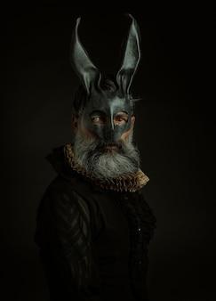 Retrato de homem gótico elegante com máscara de couro de coelho em fundo preto.