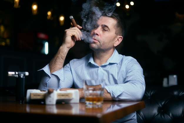 Retrato de homem hansome fumando charuto em um lounge bar