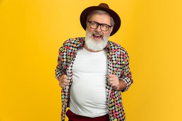 Retrato de homem hippie sênior solated em fundo amarelo.