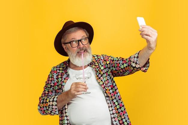 Retrato de homem hippie sênior usando dispositivos, gadgets isolados em fundo amarelo do estúdio. tecnologia e conceito de estilo de vida idoso alegre.