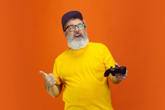 Retrato de homem hippie sênior usando dispositivos, gadgets isolados em fundo laranja do estúdio. tecnologia e conceito de estilo de vida idoso alegre.