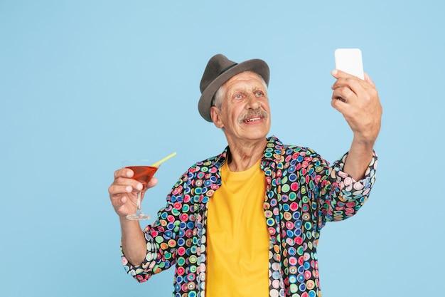 Retrato de homem hippie sênior usando dispositivos, gadgets isolados no fundo brilhante do estúdio. tecnologia e conceito de estilo de vida idoso alegre.