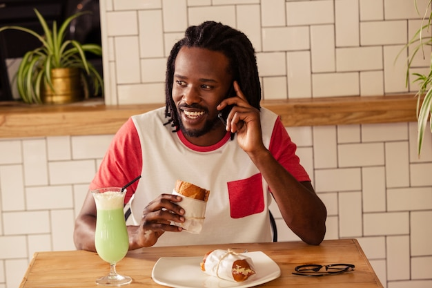 Retrato de homem hipster no telefone enquanto come