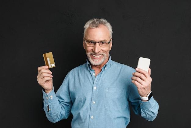 Retrato de homem idoso dos anos 70, com cabelos grisalhos e barba, segurando o cartão de crédito e smartphone para compras on-line, isolado sobre a parede preta