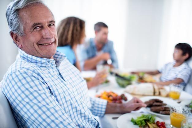 Retrato de homem idoso sentado na mesa de jantar