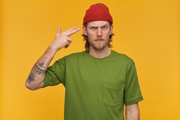 Retrato de homem infeliz com barba e cabelo loiro. vestindo camiseta verde e gorro vermelho. fazendo gesto de arma com os dedos ao lado da têmpora. isolado sobre a parede amarela
