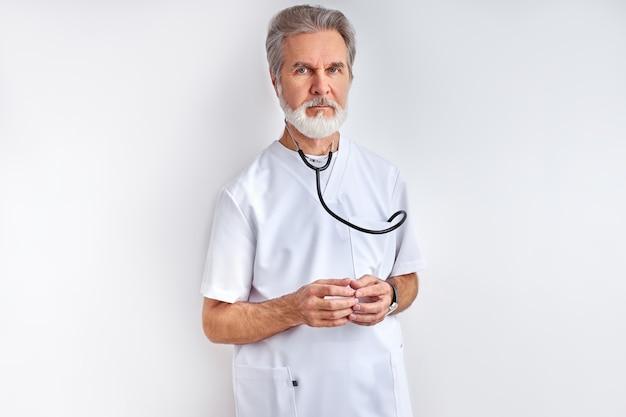 Retrato de homem inteligente médico maduro com cabelos grisalhos em uniforme médico com estetoscópio, pronto para ajudar