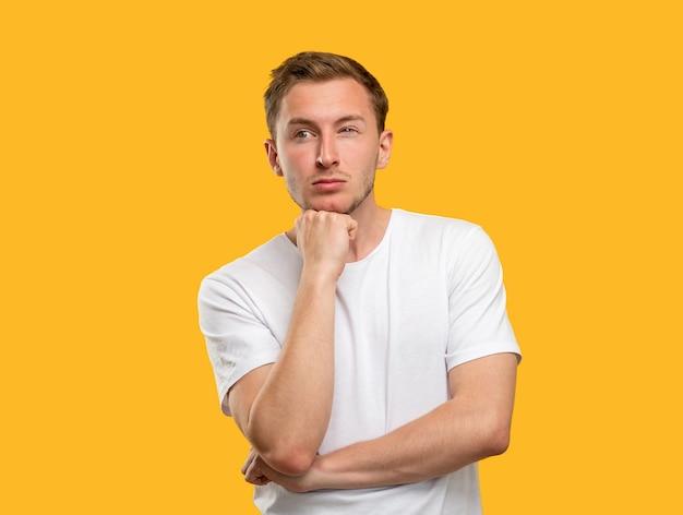 Retrato de homem intrigado. decisão difícil. cara preocupado, pensando na ideia isolada em fundo laranja.