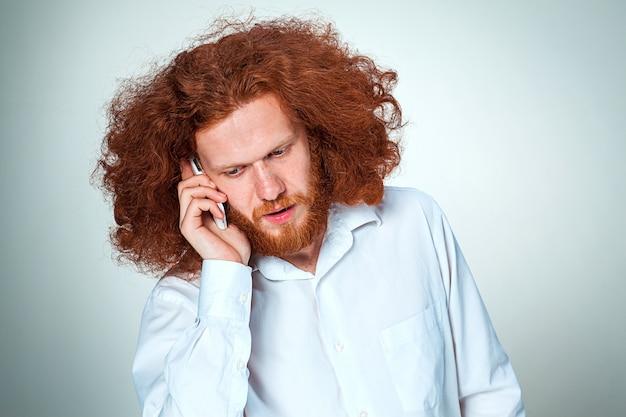 Retrato de homem intrigado, falando ao telefone, uma parede cinza