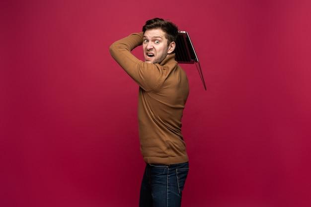 Retrato de homem irritado chateado com raiva casual gritando e segurando laptop prata isolado sobre fundo rosa.