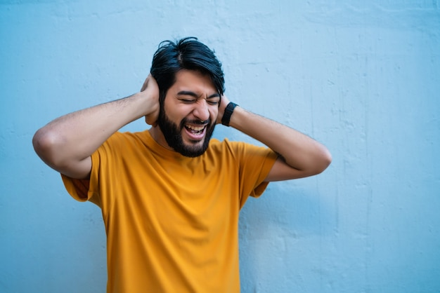 Retrato de homem irritado e estressado, cobrindo as orelhas com as mãos.