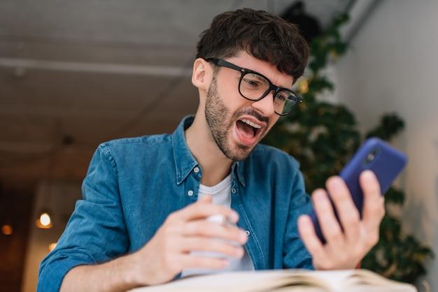 Retrato de homem irritado estressado, usando telefone celular, lendo más notícias on-line. negócio frustrado