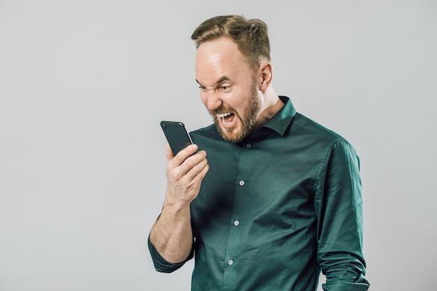 Retrato de homem irritado, gritando no alto-falante do seu smartphone