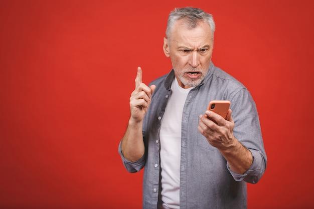 Retrato de homem irritado sênior falando no telefone móvel isolado na parede de parede vermelha. emoções negativas.