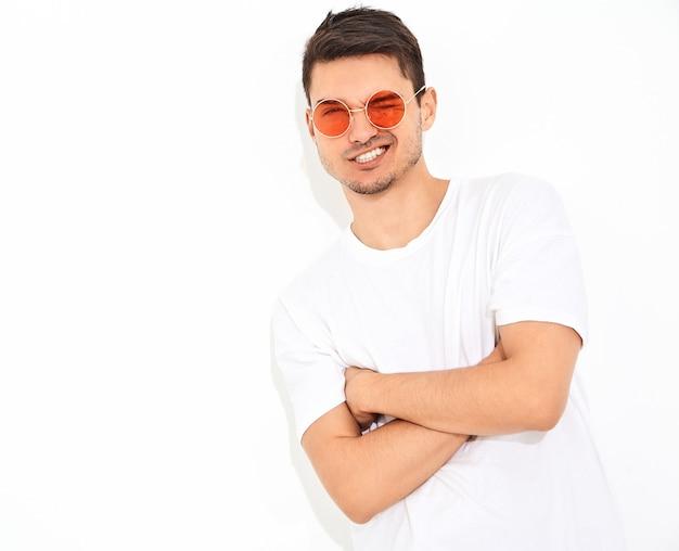 Retrato de homem jovem bonito modelo vestido com roupas jeans e camiseta posando de óculos de sol. braços cruzados